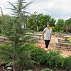 CATHY SPAULDING/Muskogee Phoenix<br /> Papilion Manager Katherine Coburn walks around the raised flowerbed she planted honoring Canada. Papilion flower beds are honoring Gardens of the World.