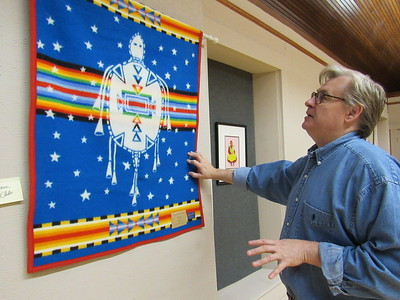 CATHY SPAULDING/Muskogee Phoenix Five Civilized Tribes Museum Executive Director Sean Barney shows how a Pendleton wool blanket made by artist Virginia Stroud still has some horse hairs. He said former Cherokee Nation Principal Chief Wilma Mankiller donated the blanket to the museum.