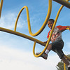 Staff photo by Cathy Spaulding<br /> Daveyn Dobard, 4, works his way across wavy high bars at Civitan Park during a warm day afternoon recently.