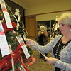 Staff photo by Cathy Spaulding<br /> Christy Biggs looks at an Angel Tree tag she picked up Friday at Arrowhead Mall. The Salvation Army kicked off its Angel Tree campaign at the mall.