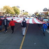 "Staff photo by Mark Hughes<br /> Volunteers hang on to a 32-foot by 62-foot American flag during Saturday's Veterans Day parade. Navy veteran Brian Phelps brought his child ""to show my daughter we should honor vets."""