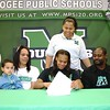 Phoenix special photo by John Hasler<br /> Muskogee's Trena Mims, center, signs her national letter of intent on Monday to play college basketball at the University of North Texas. Seated with Trena are her nephew Kayzen, mother Cynthia and father Greg Sr. Standing behind Trena is Lady Roughers' first-year head coach Shonika Breedlove.