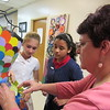Staff photo by Cathy Spaulding<br /> St. Joseph Catholic School teacher Martha Peters helps seventh-graders Abigail Carter, left, and Katie Gamblin adjust a dress made of recycled bottles and cereal boxes. The dress is a finalist in a Keep Oklahoma Beautiful Do Your Art contest.