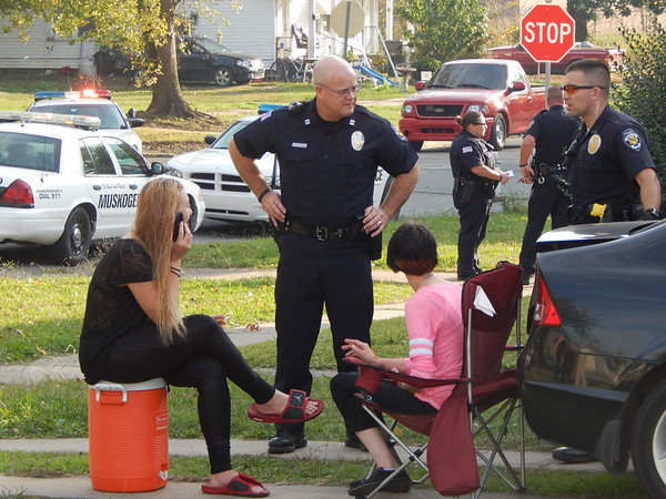 Staff photo by Mark Hughes<br /> Muskogee police officers interview residents at the 300 block of North Ninth Street, between Court and Emporia Streets following a shooting reported at 2:54 p.m. Thursday. Judy Peal was arrested around 4 p.m. Thursday on a complaint of shooting with intent to kill, said Officer Lincoln Anderson, police spokesman. A single bullet hole was discovered in the wall on the front porch of a home. There were no injuries.
