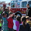 Staff photo by Cathy Spaulding<br /> Muskogee Fire Department driver Clay Waggle explains a firetruck to Ben Franklin Science Academy students Friday during a tour of different modes of transportation.