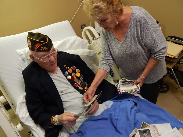 Staff photo by Mark Hughes<br /> Glenn R. Haskins, 92, and his niece, Shirley Cottingham, reminisce over photos taken during Haskins' 20-year U.S. Navy career. He served in World War II, Korean Conflict and the Vietnam War.