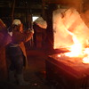 Staff photo by Mark Hughes<br /> Employees at American Foundry Group pour molten steel into castings at their foundry. AFG can produce castings from 100 pounds up to 5,000 pounds and can make up to 30,000 different parts, said Garry Hayes, general manager.