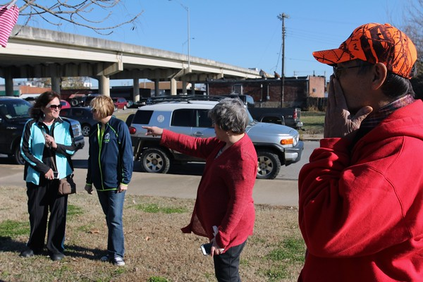 Special photo by Travis Sloat<br /> Charlie Curley, right, reacts after putting on a hand-knitted scarf from a tree near the Gospel Rescue Mission on Tuesday. The Yarn-Yarn Sisterhood, which included members Dixie Conrad, Sue Brannan and Susan Updike, spent Tuesday afternoon hanging up donated and handmade items in different locations around Muskogee<br /> for homeless people in the city.