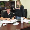 Staff photo by Cathy Spaulding<br /> Lance Bowden and his wife Lauren Bowden, go over business paperwork. Bowden bought a pest control business from his grandfather.