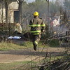 Staff photo by Harrison Grimwood<br /> A volunteer firefighter runs back to the scene of a fatal fire, now a smoldering building, as his fellow firefighters try to clear out smoke so investigators can enter the building.