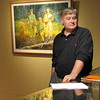 Staff photo by Cathy Spaulding<br /> Five Civilized Tribes Museum Executive Director Sean Barney stands by a Gary Montgomery painting, one of 28 entries in the museum's Masters Art Show, which runs through November.
