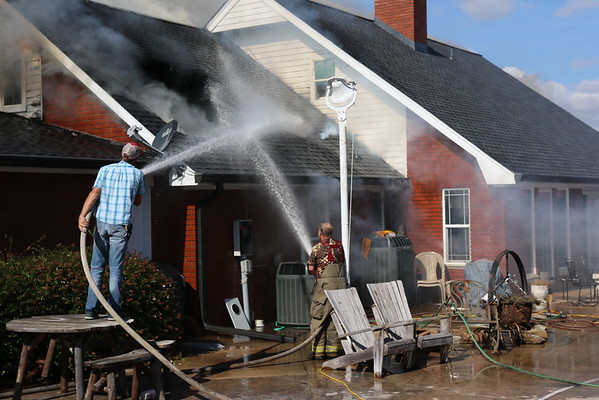 Staff photo by Harrison Grimwood<br /> Volunteer firefighters spread water across a roof and in an opening where the fire apparently burned through the roof.
