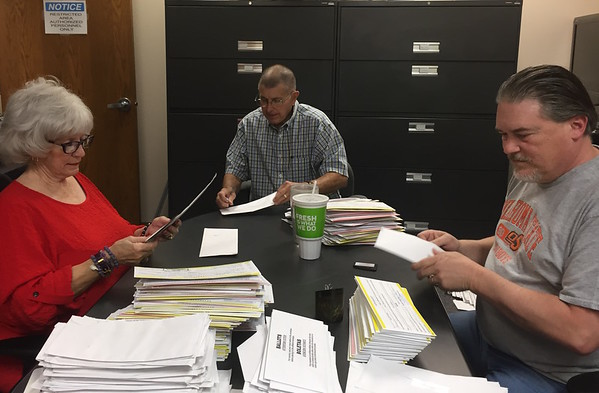 Staff photo by D.E. Smoot<br /> Muskogee County Election Board members, from left, Evelyn Hibbs, Andy Ewing and Secretary Kelly Beach open and inspect absentee ballots received by mail during a special meeting Monday afternoon.