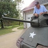 Staff photo by Cathy Spaulding<br /> Joe Rybolt gets into his tank through the top turret. He made the tank frame with an old tractor crate.