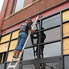Staff photo by Cathy Spaulding<br /> Brad McGuire of Hill Glass & Door installs windows Monday at Bro's Haberdashery, a men's clothing store which opened Thursday at 105 N. Main St. According to the store's website, a haberdasher's job is to sell to customers in a welcoming manner.