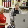 Staff photo by Harrison Grimwood<br /> A Muskogee County election official aids Eva Farguson, right, in scanning her ballot Tuesday night at the American Legion Post 15 precinct.
