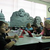 Staff photos by Cathy Spaulding<br /> A large picture of the Pearl Harbor Monument provides a backdrop for Hilldale Upper<br /> Elementary teacher Lauren Evans as she teaches. Evans bought a set of massive pictures of U.S. monuments through the Hilldale Education Foundation.