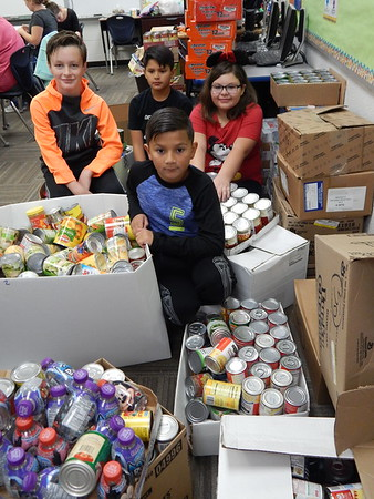 Staff photo by Cathy Spaulding<br /> Tony Goetz Elementary fifth-graders, Krew Thompson, front and, back row, from left, Van Elgin, Gabriel Quemada and Trinity Knott show a portion of the 2,176 cans their class collected for a can drive. Students collected 5,097 cans for the Community Food Pantry. The top three casses: Shelby Castleberry's fifth-grade class collected 2,176 of those cans. Dannon Ellis' third graders collected 942, and Lorie Greathouse's fourth graders collected 916.