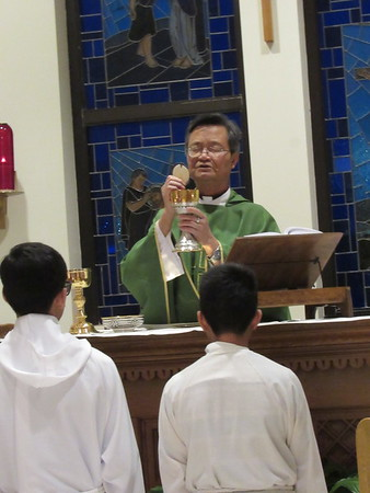 Staff photo by Cathy Spaulding<br /> Altar boys kneel while the Rev. Tam Nguyen prepares the Eucharist during a Vietnamese service at St. Joseph Catholic Church.