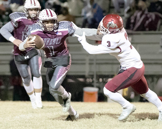 SHANE KEETER/Special to the Phoenix Eufaula's Nick Jones gets around Spiro's Will Dunigan during Friday's Class 2A first-round playoff game in Eufaula. The Ironheads won 27-0 to advance.