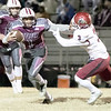 SHANE KEETER/Special to the Phoenix<br /> Eufaula's Nick Jones gets around Spiro's Will Dunigan during Friday's<br /> Class 2A first-round playoff game in Eufaula. The Ironheads won 27-0 to advance.