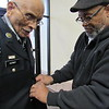 Staff photo by Cathy Spaulding<br /> Larry Foye' helps retired U.S. Army Sgt. 1st Class Herman Kirby put on his replacement uniform. Kirby lost his original uniform, medals and memorabilia in a fire.