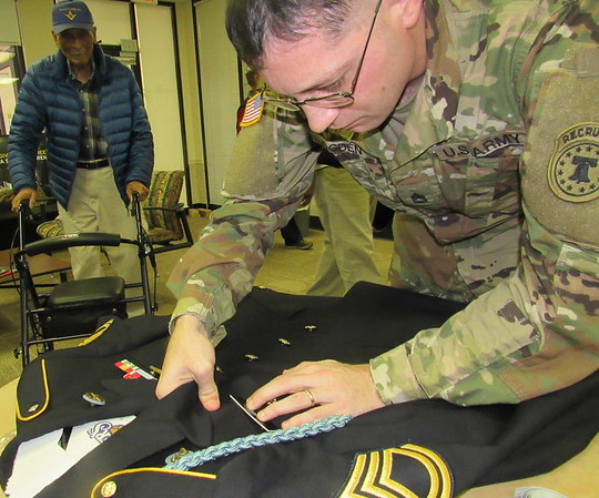 Staff photo by Cathy Spaulding<br /> Retired U.S. Army Sgt. 1st Class Herman Kirby watches Sgt. 1st Class Gordon Ogden put medals on a uniform. Kirby lost his original Korean and Vietnam war medals in a fire.