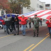 Special photo by Chesley Oxendine<br /> Members of the U.S. Department Of Veterans Affairs office bring a garrison-sized United States flag down Broadway Avenue during Saturday's parade, despite chilly winds.