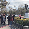 "CHESLEY OXENDINE/Muskogee Phoenix<br /> A gathered crowd snaps pictures with the restored ""Spirit of An American Doughboy"" statue outside Jack C. Montgomery VA Medical Center. The impromptu photoshoot followed a rededication ceremony celebrating the statue's restoration."