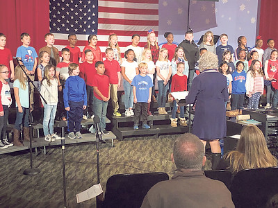 """CHESLEY OXENDINE/Muskogee Phoenix Third and fourth graders from Sadler Arts Academy perform """"For The Good of The Many,"""" part of several songs sung during a special Veterans Day service. The event included songs and percussion performed by the students, as well as a lesson on the USS Batfish, among other presentations. The students sang and spoke to a packed auditorium and delivered roses to attending veterans."""