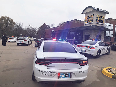 CHESLEY OXENDINE/Muskogee Phoenix Police gather outside I Don't Care Bar and Grill at the scene of an officer-involved shooting Monday afternoon. The shooting occurred while officers were serving a warrant to Andrew Kana, of Ponca City, who allegedly pulled a gun on police while they were arresting him.