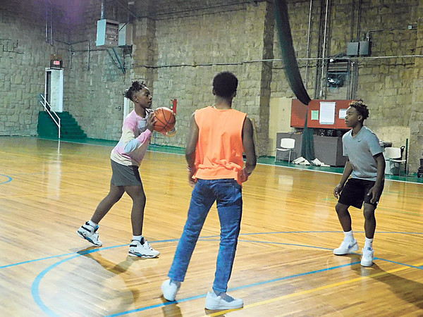 KENTON BROOKS/Muskogee Phoenix<br /> Muskogee High School ninth-graders enjoy an afternoon of basketball on Tuesday inside the Teen Center on Callahan Street. The trio, from left, are DeShawn Smith, Rayesean Ellis and Walker Newton. Though the weather outside was cold and dipped below 20 degrees in the morning, it was nice and warm inside as Muskogee High School students played some pick-up basketball. The center is open after school, and students gather there to play games, watch TV or other activities until it's time to go home.