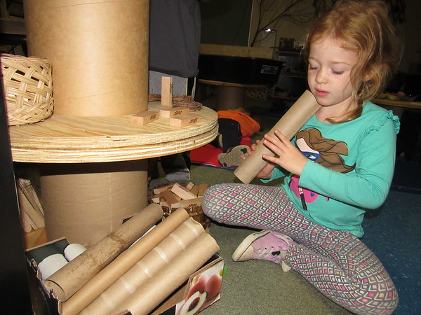 """Staff photo by Cathy Spaulding<br /> Early Childhood Center pupil Caroline Jones peers through a paper towel tube, one of the """"natural materials"""" she and her classmates use in creative play. The classroom also features blocks, rocks, beads and sticks as play materials."""