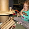 "Staff photo by Cathy Spaulding<br /> Early Childhood Center pupil Caroline Jones peers through a paper towel tube, one of the ""natural materials"" she and her classmates use in creative play. The classroom also features blocks, rocks, beads and sticks as play materials."