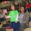 Staff photo by Cathy Spaulding<br /> Laela Bear, 4, joins in the flag-waving as she stands by her mother, Sylvia Bear, at Fort Gibson's all-district Veterans Day assembly on Friday.