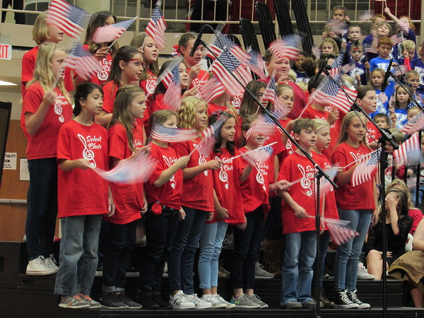 """Staff photo by Cathy Spaulding<br /> Intermediate Select Choir singers wave flags while singing George M. Cohan's """"Grand Old Flag,"""" during the all-district Veterans Day assembly.<br /> Early Learning Center and High School choirs sang, too."""