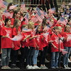 "Staff photo by Cathy Spaulding<br /> Intermediate Select Choir singers wave flags while singing George M. Cohan's ""Grand Old Flag,"" during the all-district Veterans Day assembly.<br /> Early Learning Center and High School choirs sang, too."