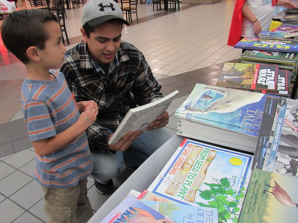 Staff photo by Cathy Spaulding<br /> Chris Finsand shows a book to Jeremiah Finsand, 5,during the literacy event.
