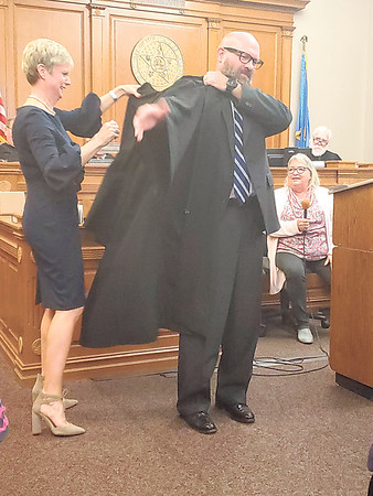CHESLEY OXENDINE/Muskogee Phoenix<br /> Anne King helps her husband, newly appointed Muskogee County District Court Judge Tim King, put on his judicial robes while Muskogee County Court Clerk Paula Sexton and retired District Judge Tom Alford look on.