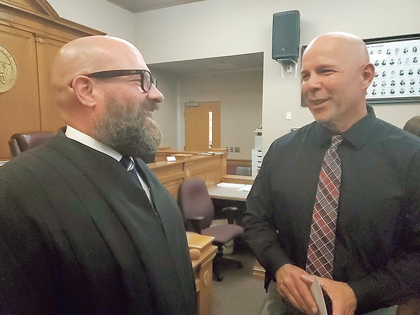Newly appointed Muskogee County District Court Judge Tim King chats with Muskogee Police Department Chief Johnny Teehee.