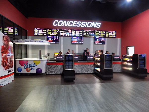 Staff photo by Mike Elswick<br /> Epic Cinema Muskogee employees staff the concession at the theater, which opened Tuesday. In addition to traditional movie show offerings of candy, soft drinks and popcorn, guests can order wraps, pizza and sandwiches served on trays so they can dine while they watch the movie.