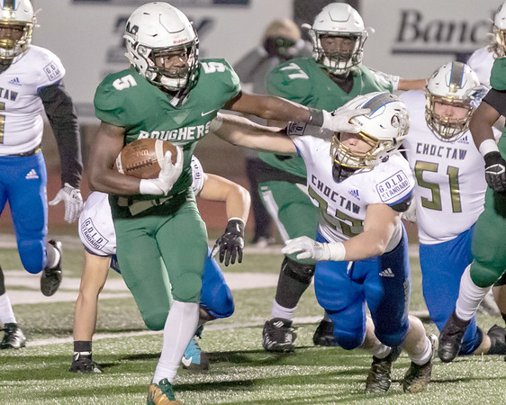 SHANE KEETER/Muskogee Phoenix<br /> Muskogee's Jimmie Coleman stiff arms Choctaw's Jeff Roberson during the Roughers' 29-21 loss in the first round of the Class 6A-II playoffs on Friday at Indian Bowl. Story in Sports.