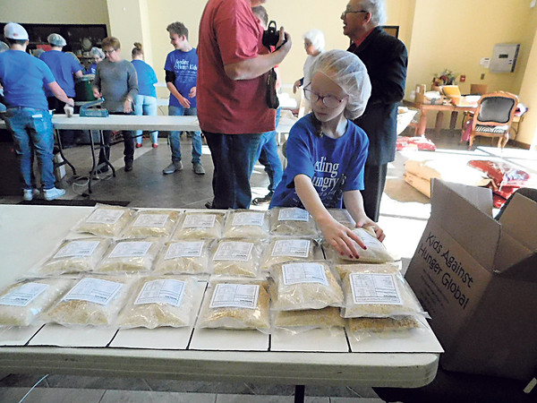 KENTON BROOKS/Muskogee Phoenix<br /> Boulevard Christian third-grader Brooklyn Steelher, 8, helps pack bags of food Friday that are being used to help those in need in Muskogee and the Bahamas.