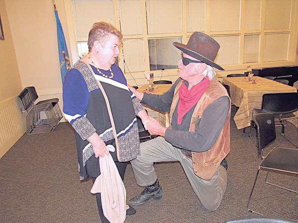 """CATHY SPAULDING/Muskogee Phoenix<br /> Ann Barker Ong gets a birthday serenade from fictitious lawman Rooster Cogburn (portrayed by Clarance Banes) during a Friday reception marking the world premiere of """"Hell on the Border"""" held at Three Rivers Museum. The movie depicts the exploits of Territorial lawman Bass Reeves, who served the Muskogee area."""