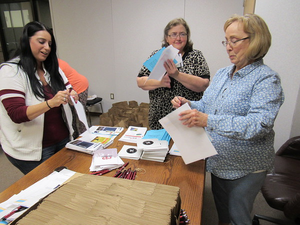 Staff photo by Cathy Spaulding<br /> Volunteers, from left, Crystal Richerson, Wanda Fulkerson and Julie Whittenberg assemble material from five churches to go in goody bags to be distributed Saturday during the Hands Halting Hunger drive-through food giveaway.