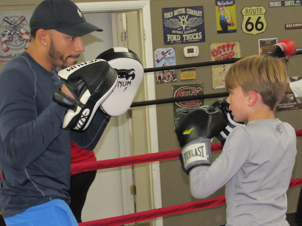 "CATHY SPAULDING/Muskogee Phoenix<br /> Alfred Walker, left, teaches Sebastian Clinkenbeard, 9, punching techniques during a recent class. He said he seeks to instill a ""don't quit"" attitude."