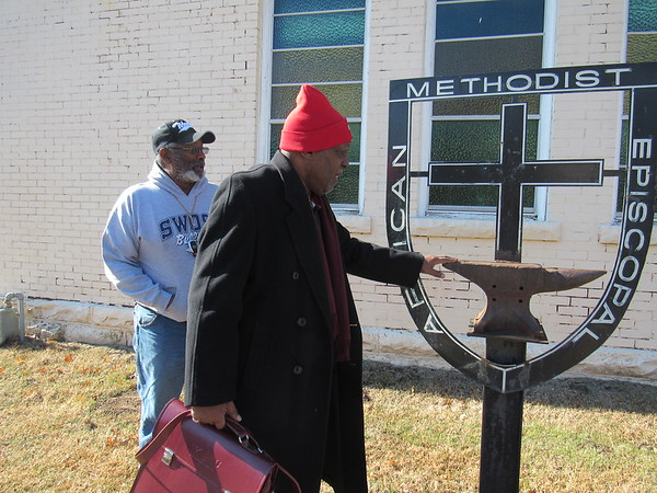 CATHY SPAULDING/Muskogee Phoenix<br /> Ward Chapel African Methodist Episcopal Church member Leo Bray, left, and pastor Samuel Craig inspect the church sign. The anvil represents the denomination's founding in a blacksmith shop in the late 1790s.