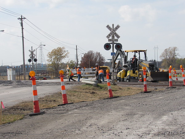 Staff photo by Cathy Spaulding<br /> Work on the railroad crossing caused a slight detour on the access road to Three Forks Harbor, just south of U.S. 62, this week. Workers install a concrete slab into tracks leading into the OG&E Power Plant on Friday.