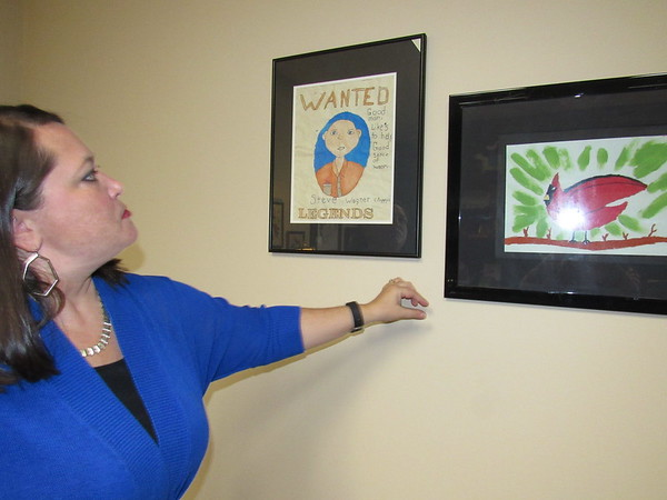 CATHY SPAULDING/Muskogee Phoenix<br /> Lynn Wallis admires art work done by her daughter. It hangs in her office at Edward Jones.