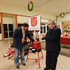 KENTON BROOKS/Muskogee Phoenix<br /> Jason Hughes, the incoming market president at Bank of Oklahoma, makes the first contribution of $2,000 to the Red Kettle as part of Saturday's Angel Tree and Kettle Kickoff in front of Dillard's inside Arrowhead Mall. Lt. Charles Smith, one of the commanding officers at Muskogee's Salvation Army, said this year's goal for the Red Kettle in Muskogee is $70,000.